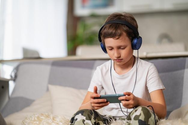Niño con auriculares y teléfono inteligente en sus manos está sentado en el sofá y jugando.