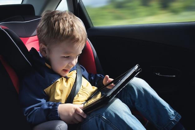 Niño en el automóvil con tablet pc
