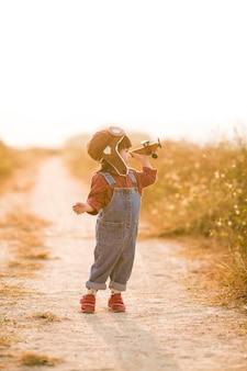 Niño con avión de juguete en la naturaleza al atardecer