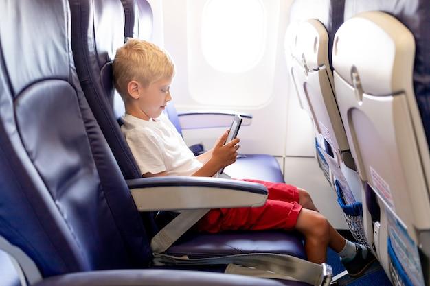 Un niño en un avión leyendo un libro electrónico o jugando con una tableta en un vuelo largo