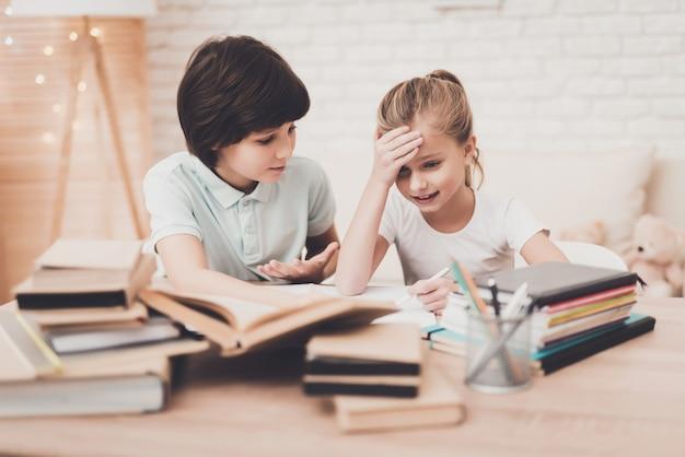 Niño ayuda a niña frustrada a hacer la tarea