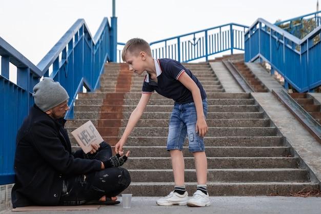 El niño ayuda a las personas sin hogar en la calle.