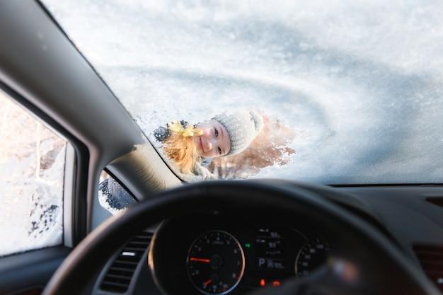 El niño ayuda y raspa la nieve y el hielo de la ventana del automóvil