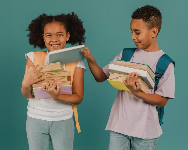 Niño ayudando a su amigo con los libros.