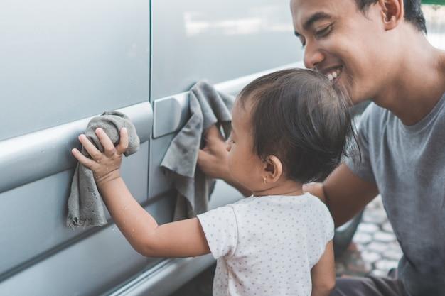 Niño ayudando a su papá a limpiar el auto