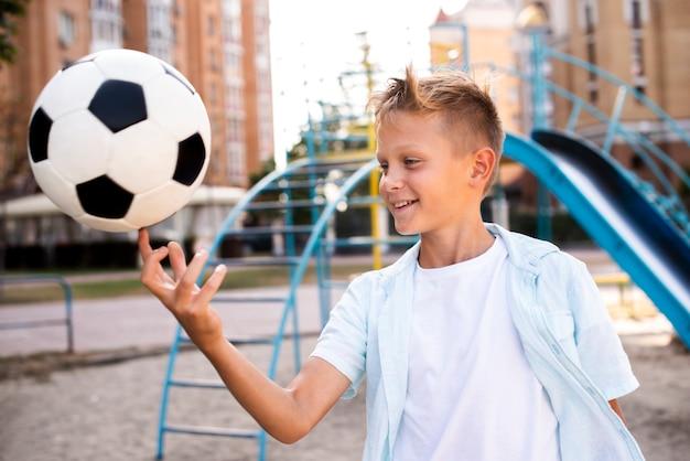 Niño con balón de fútbol en un dedo