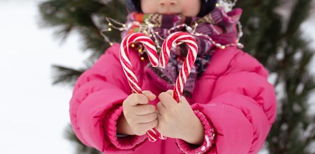 Niño con bastones de caramelo grandes. concepto de navidad.