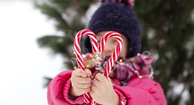 Niño con bastones de caramelo grandes sobre fondo borroso. concepto de vacaciones de invierno.