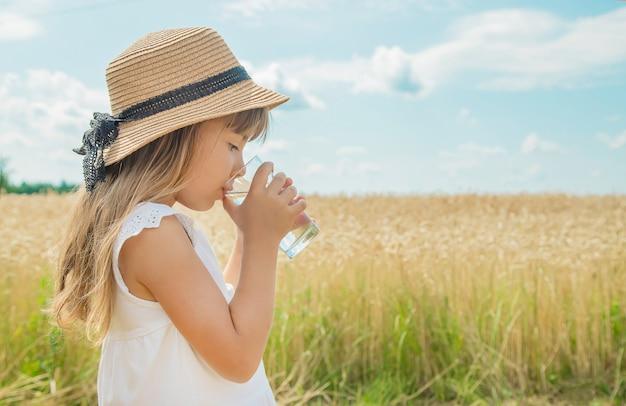 Un niño bebe agua en el fondo del campo