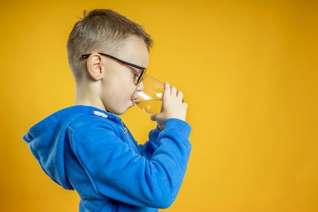 Un niño bebe agua en una pared turquesa.