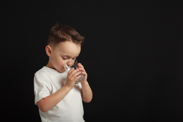 Un niño bebe agua sobre un negro.