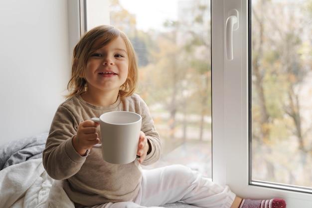 Niño bebe cacao o leche cerca de la ventana de una gran taza blanca.