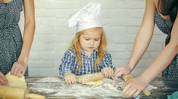 Niño bebé con gorro de cocinero rodando masa