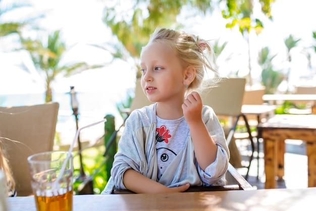 Un niño bebe jugo de vacaciones.