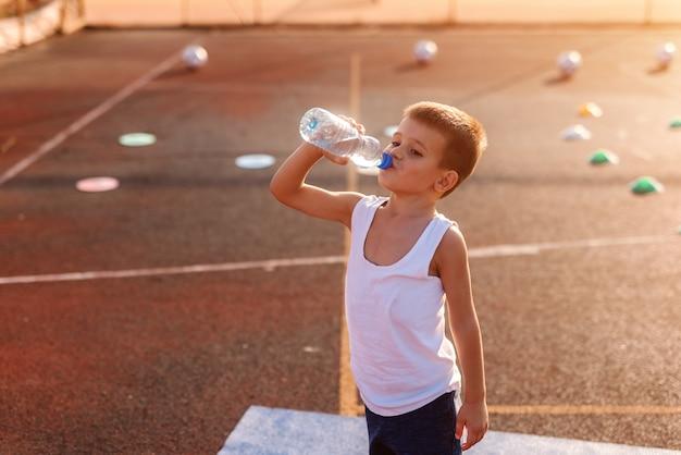 Niño bebiendo agua de botella y de pie en la cancha después de hacer ejercicio.
