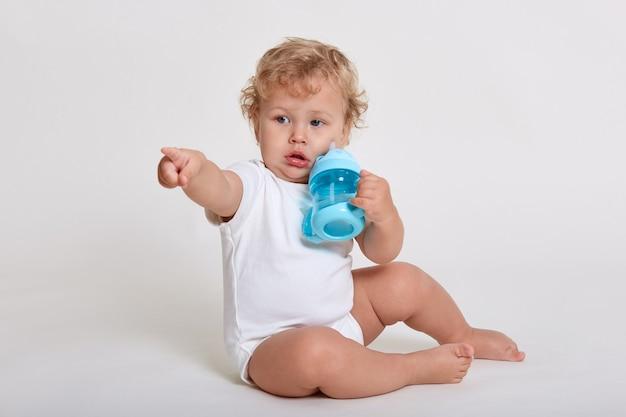 Niño bebiendo agua mientras está sentado en el piso aislado sobre un espacio en blanco, mirando y apuntando hacia otro lado, vistiendo traje de cuerpo