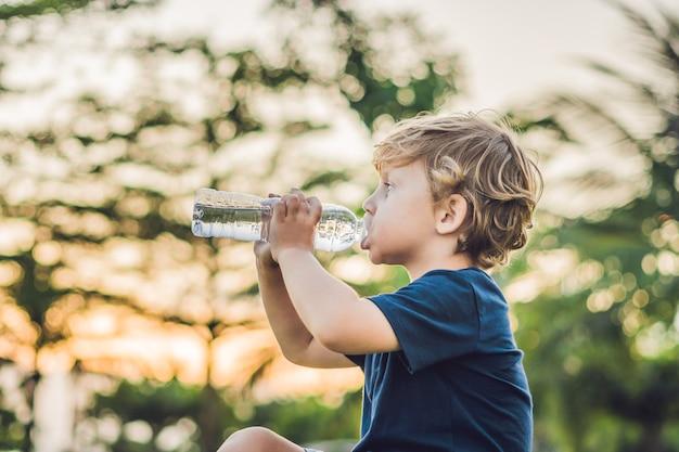 Niño bebiendo agua en la naturaleza