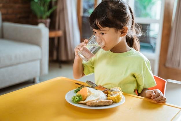 Niño bebiendo mientras desayuna saludable