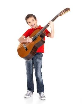 Niño blanco canta y toca la guitarra acústica aislada en blanco