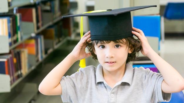Niño blanco sonriente con la gorra de graduación