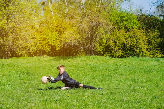 Niño bloqueando el balón con las manos