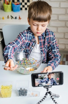Niño con bolas de hidrogel en tazón y teléfono