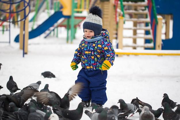 Niño bonito alimenta pájaros en el parque de nieve de invierno al aire libre