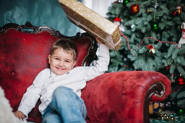 El niño bonito se sienta en la silla