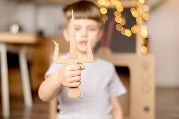Niño borroso con daga de cartón