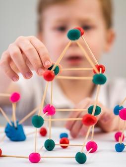Niño borroso jugando con colorido juego de átomos