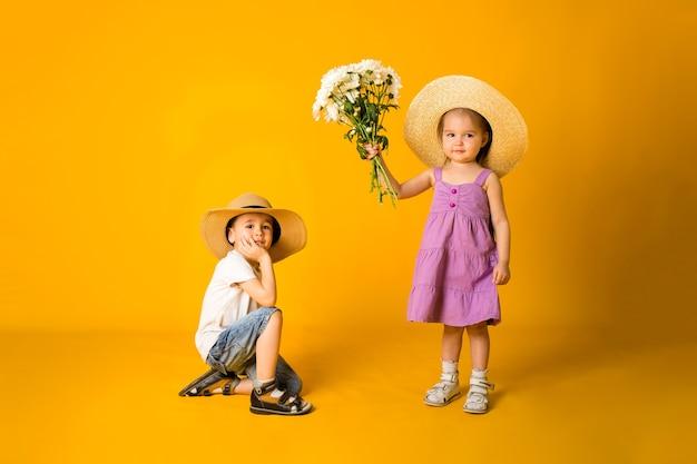 Un niño caballero se sienta en su rodilla y una niña dama con flores de pie sobre una superficie amarilla con espacio para texto