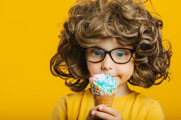 Niño con cabello largo come felizmente helado