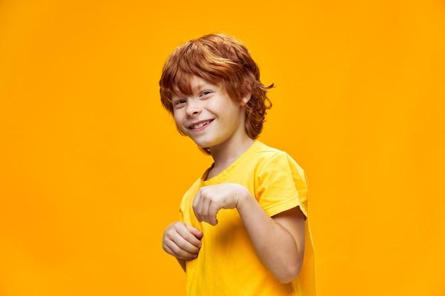 Un niño con cabello rojo sonríe y sostiene la palma de su mano doblada