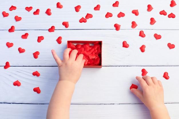 Niño con caja de regalo y corazones para el día de la madre sobre fondo de madera blanco concepto de boda y san valentín