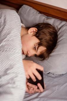 Niño en la cama jugando en el móvil