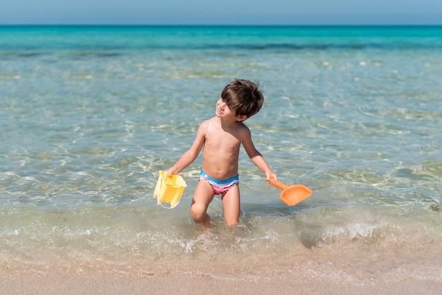 Niño caminando con juguetes en el agua en la playa