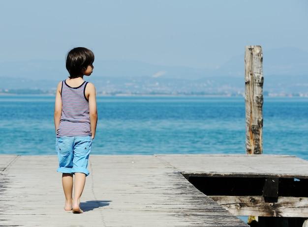 Niño caminando en el muelle por el mar hermoso