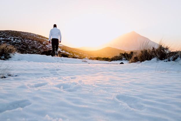 Niño caminando por la nieve al atardecer