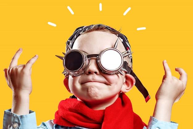 Niño con camisa azul, bufanda roja, gafas de motorista y pañuelo en brillante