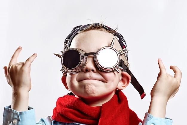 Niño con camisa azul, bufanda roja, gafas de motorista y pañuelo sobre fondo claro