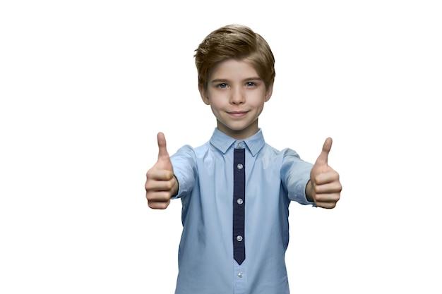 Niño con camisa azul mostrando bien con ambas manos en la pared blanca