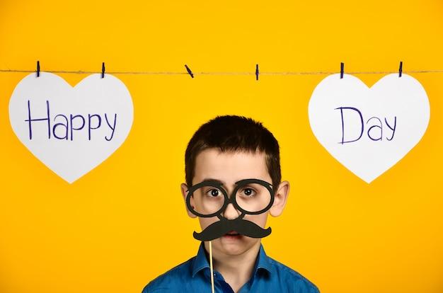 Un niño con una camisa azul sobre un fondo amarillo con un corazón y una inscripción, un día festivo está torcido y viste gafas y bigote