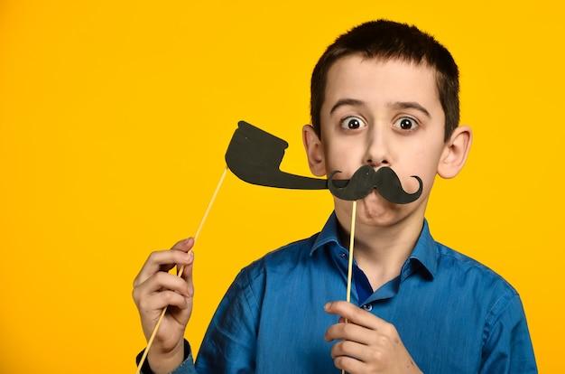 Un niño con una camisa azul sobre un fondo amarillo hace una mueca y viste un bigote y sostiene una pipa