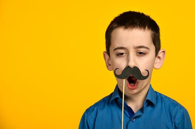 Un niño con una camisa azul sobre fondo amarillo está retorcido y viste su bigote