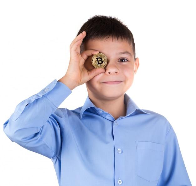 Niño con camisa azul sostiene bitcoin frente a sus ojos y sonríe