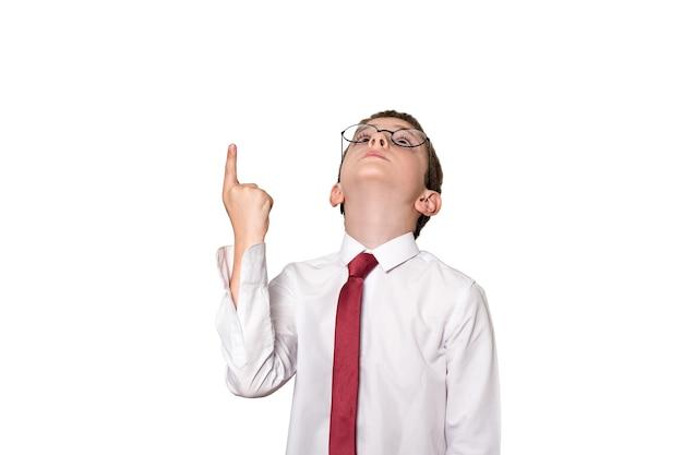 El niño con una camisa blanca y gafas señala con el dedo hacia arriba. concepto de escuela. aislar