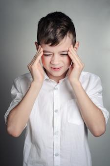 Un niño en una camisa blanca sufre de un dolor de cabeza. retrato de estudio