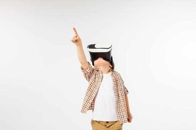 Niño en camisa a cuadros con gafas de casco de realidad virtual, apuntando hacia arriba