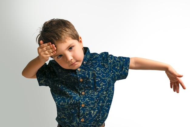 Un niño con una camisa sobre fondo blanco.