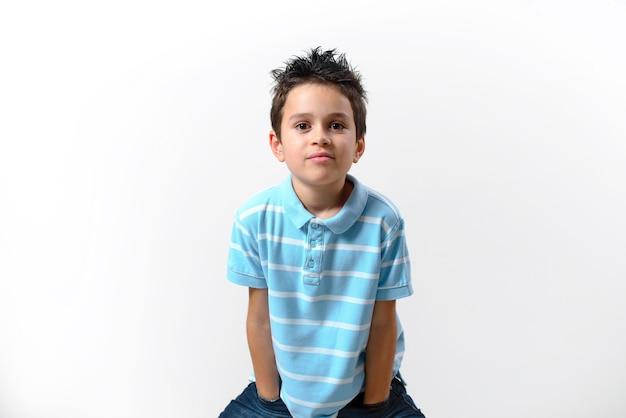 El niño con una camiseta azul está de pie con las manos en los bolsillos inclinados y mira directamente a la cámara.